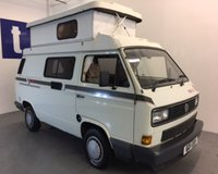 "USED 1989 VOLKSWAGEN TRANSPORTER 1.9 CARAVAN 1d  Stunning Volkswagen T25 Holdsworth ""Villa 3"" Hi Top Camper Van Finished in Gleaming Pastel White With Contrasting 1990's Retro Body Striping And Beige Draylon Upholstery, Just 70,250 Miles With Only 2 Owners From New, Massive Service File That Includes The Original Service Book With 15 Stamps Up Till 2009 And Then A Huge File That Includes All The Bills For The Last 10 Years And Even The Original Bill Of Sale, In Really Very, Very Good Original Order Throughout"