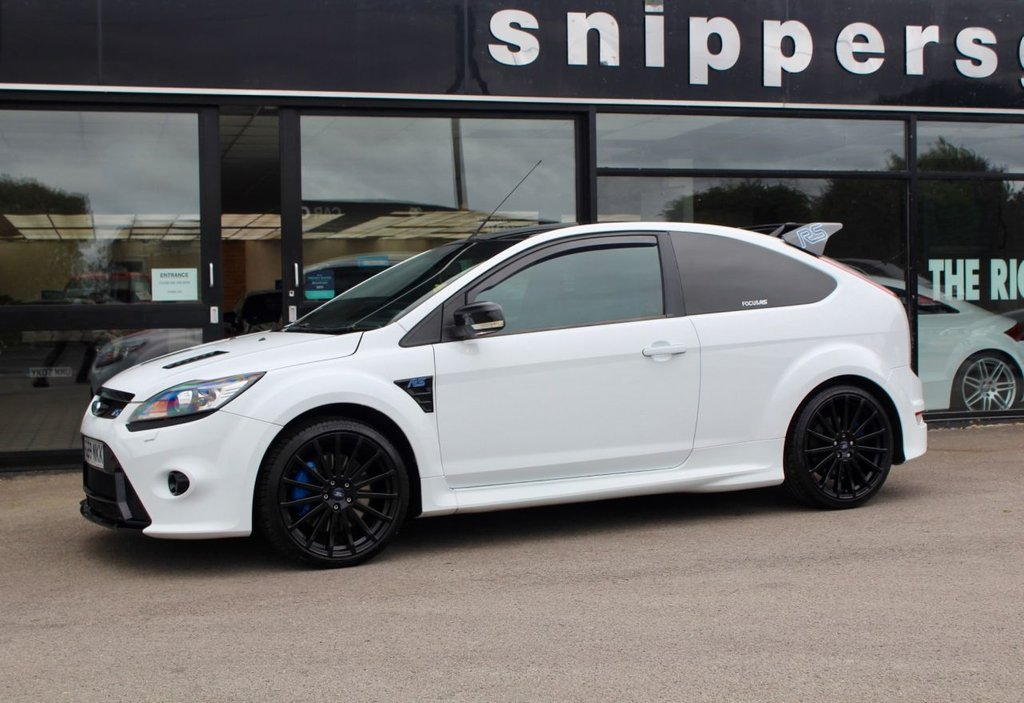 USED 2009 59 FORD FOCUS 2.5 RS 3d 300 BHP Great Example Frozen White Focus RS, Rear Parking Sensors,Air-Conditioning, Alarm, Alloy Wheels (19in), Heated Front Screen, In Car Entertainment (Radio/CD Autochanger/MP3), Tinted Glass. 4 seats,  Air conditioning - CFC-free, Easy fuel capless refuelling system, Electric hydraulic power assisted steering, Electronic stability programme with traction control + emergency brake assist, Front Recaro sports seats, 'Ford Power' starter button, Perimeter alarm with volume sensing, Xenon headlights.