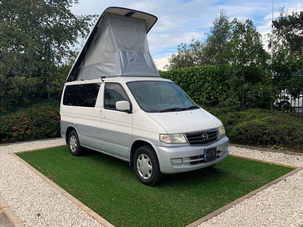 USED 2018 T MAZDA BONGO 2.5  A Well Equipped 8 Seat Example with a Versatile Cabin Layout and a Full Electric Elevating Roof. This Popular MPV comes with the Desirable Automatic Gearbox and the More Powerful 2.5 litre V6 engine. Features Include Electric Blinds, Digital Climate Control, Rear Privacy Glass, Radio and CD Player. These Popular Bongos are Renowned for their Reliability and this Particular Example would make a Sound Platform for a Campervan Conversion.