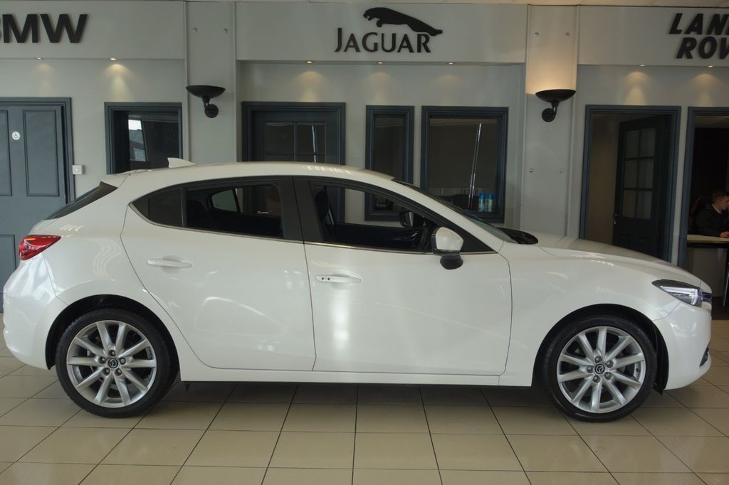 USED 2018 18 MAZDA 3 2.0 SPORT NAV 5d AUTO 118 BHP FINISHED IN STUNNING PEARL WHITE WITH FULL BLACK LEATHER HEATED SEATS WITH ELECTRIC ADJUSTMENT + SATELLITE NAVIGATION + DAB DIGTAL RADIO + BLUETOOTH MEDIA + REAR VIEW CAMERA + HEATED STEERING WHEEL + HEADS UP DISPLAY + KEYLESS START + VOICE COMMAND + PRIVACY GLASS + FRONT/REAR PARK ASSIST + PADDLE SHIFT GEARS + SELECTABLE DRIVING MODES + POWER FOLDING MIRRORS + MATT GREY INTERIOR TRIM + AUTO LIGHTS + BOSE SOUND SYSTEM + DUAL ZONE AIR CONDITONING + CLIMATE CONTROL + IN CAR ENTETAINMENT AUX-USB +