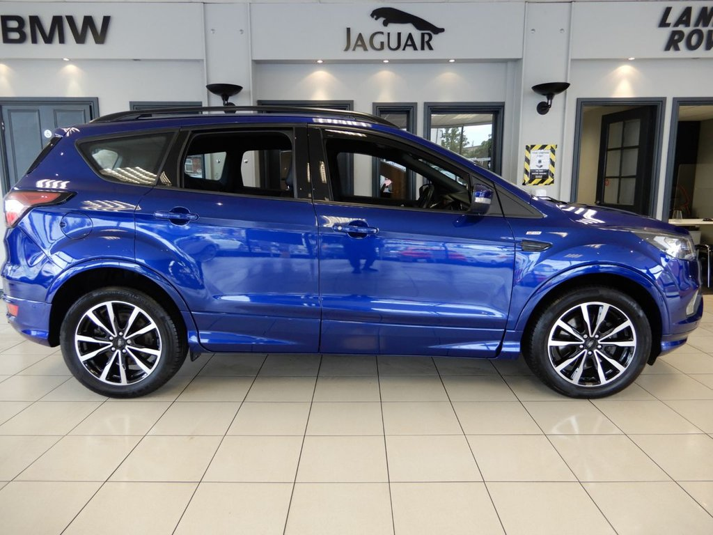 USED 2017 17 FORD KUGA 1.5 ST-LINE TDCI 5d AUTO 119 BHP FINISHED IN STUNNING METALLIC BLUE AND COMPLIMENTED BY BLACK PART LEATHER SEATS AND UPHOLSTERY + BEAUTIFUL CAR + 1 OWNER FROM NEW WITH A FORD MAIN DEALER SERVICE HISTORY + SATELLITE NAVIGATION + DAB DIGITAL RADIO + SONY SOUND SYSTEM + BLUETOOTH PHONE AND MEDIA + CRUISE CONTROL + VOICE COMMAND + AUTOMATIC LIGHTS WITH LED DAYTIME RUNNING LIGHTS + POWER TAIL GATE + ACTIVE PARK ASSIST + PARKING SENSORS + ISOFIX POINTS + 60/40 FOLDING REAR SEATS + UNMARKED 2 TONE DIAMOND CUT ALLOY WHEELS + TWIN CUPHO