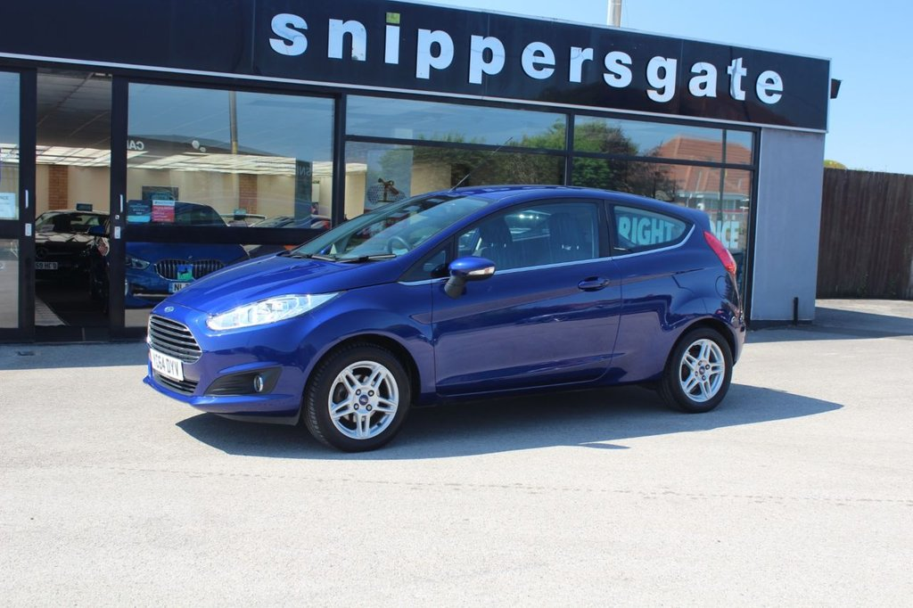 USED 2014 64 FORD FIESTA 1.0 ZETEC 3d 99 BHP Deep Impact Blue Metallic, Heated Windscreen, Rear Spoiler, Remote Central Locking, Tyre Pressure Monitoring, Steering Wheel Mounted Controls, ESP + Traction Control, LED Daytime Running Lights, DAB Radio, Bluetooth Phone, USB Connection, Electric Windows, Full Service History.
