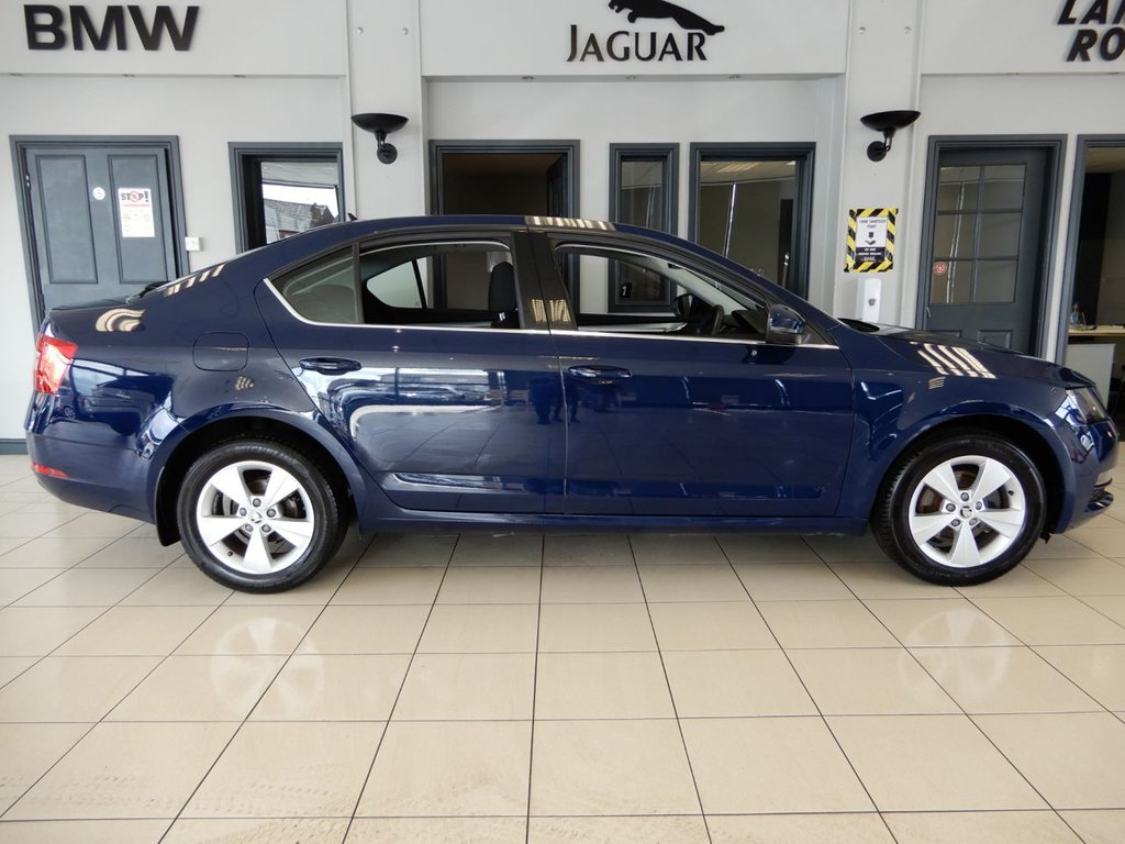 USED 2018 67 SKODA OCTAVIA 1.0 SE TECHNOLOGY TSI DSG 5d AUTO 114 BHP FINISHED IN STUNNING DARK METALLIC BLUE WITH TWO TONE DARK GREY CLOTH SEATS + 1 OWNER FROM NEW AND COMES WITH A FULL SERVICE HISTORY AND THE BALANCE OF THE MANUFACTURERS WARRANTY UNTIL FEB 2021 + SATELLITE NAVIGATION + APPLE CARPLAY + MIRROR LINK + ANDROID AUTO + CRUISE CONTROL + BLUETOOTH PHONE CONNECTIVITY AND BLUETOOTH MEDIA + CLIMATE CONTROLLED AIRCONDITIONING + DAB DIGITAL RADIO + ELECTRIC WINDOWS + ELECTRIC MIRRORS + UNMARKED ALLOY WHEELS + PARKING SENSORS + AUX/USB CONNECTION + ULEZ EXEMP