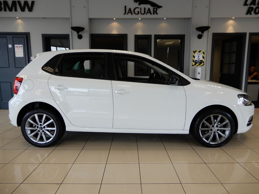 USED 2016 16 VOLKSWAGEN POLO 1.2 SE DESIGN TSI DSG 5d AUTO 90 BHP FINISHED IN STUNNING WHITE WITH CONTRASTING BLACK CLOTH SEATS + WONDERFUL SPECIFICATION POLO IN SHOWROOM CONDITION + SATELLITE NAVIGATION + FULL VOLKSWAGEN MAIN DEALER SERVICE HISTORY + REAR CAMERA + TOUCH SCREEN MEDIA DISPLAY + BLUETOOTH MEDIA + DAB DIGITAL RADIO + DUAL ZONE AIR CONDITIONING + CLIMATE CONTROL + CRUISE CONTROL + IN CAR ENTERTAINMENT AUX/USB + RAIN SENSORS + FRONT AND REAR FOGLIGHTS + ELECTRIC WINDOWS AND MIRRORS + FRONT AND REAR PARKING SENSORS + UNMARKED ALLOY WHEELS + ULEZ COM