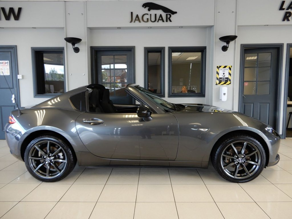 USED 2018 67 MAZDA MX-5 2.0 RF SE-L NAV 2d 158 BHP FINISHED IN STUNNING METALLIC GREY COMPLIMENTED BY DARK GREY CLOTH SEATS AND GLOSS BLACK 17 INCH MULTISPOKE ALLOY WHEELS + 1 FORMER KEEPER (2 IN TOTAL) AND BEAUTIFULLY CARED FOR + SATELLITE NAVIGATION + BLUETOOTH PHONE CONNECTIVITY AND BLUETOOTH MEDIA + DAB DIGITAL RADIO + ECO STOP/START FUNCTION + VOICE COMMAND + CLIMATE CONTROLLED AIR CONDITIONING + ELECTRICALLY ADJUSTABLE MIRRORS + ELECTRIC WINDOWS + MULTI FUNCTION STEERING WHEEL + AUX CONNECTION + CD/USB MEDIA + CRUISE CONTROL