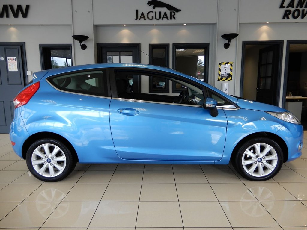 USED 2011 11 FORD FIESTA 1.4 ZETEC 16V 3d 96 BHP FINISHED IN A STUNNING METALLIC BLUE METALLIC WITH CONTRASTING BLACK CLOTH SEATS + AN ASTONISHINGLY BEAUTIFUL LOW MILEAGE GEM WITH AN ABSOLUTELY IMPECCABLE FULL SERVICE HISTORY + 1 OWNER SINCE 2011 AND IN A WONDERFUL, SHOWROOM CONDITION THROUGHOUT + REAR PARKING SENSORS + XENON HEADLIGHTS + AIR CONDITIONING + ELECTRIC WINDOWS + ELECTRIC POWER FOLDING MIRRORS + UNMARKED ALLOY WHEELS + MULTI FUNCTION STEERING WHEEL + HEATED WINDSCREEN + RADIO/CD IN CAR ENTERTAINMENT