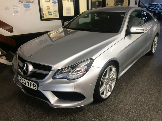 """USED 2013 63 MERCEDES-BENZ E-CLASS 2.1 E220 CDI AMG SPORT 2d 170 BHP This Mercedes E-Class Coupe has just had wheels refurbished is finished in Metallic Silver with Black full leather heated partially electric seats. It is fitted with power steering, remote locking, electric windows mirrors with power fold and part front seats, climate control, cruise control, Satellite Navigation, Bluetooth, front and rear parking sensors, AMG 19"""" alloy wheels, CD Stereo with Aux port and more. It has been privately owned from new and comes with a full service history."""