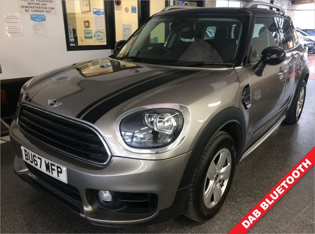 """USED 2017 67 MINI COUNTRYMAN 1.5 COOPER 5d 134 BHP Fitted with factory Panoramic glass roof, this high seated petrol powered Fully Automatic Mini Countryman is finished in Metallic Melting Silver with black pack, bonnet stripes/mirrors and roof, along with black leather & cloth heated sport seats. It is fitted with media and navigation pack,  remote locking (2 keys), anti collision warning, cruise control, electric windows and power folding mirrors, air conditioning, Bluetooth, 16"""" 5 spoke alloy wheels, Daylights, rear park assist & More."""