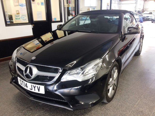 USED 2014 14 MERCEDES-BENZ E-CLASS 2.1 E220 CDI SE 2d 170 BHP With over £2000 of extras, this Convertible Mercedes E-Class 220 CDi SE Auto with paddle shift is finished in Metallic Obsidian Black with Black heated leather seats. It is fitted with fully electric convertible roof, neck scarf, heated seats,  remote locking, electric windows mirrors with power fold and part front seats, LED Daylights and xenon headlights, climate control, cruise control, Mercedes Satellite Navigation, Bluetooth, front and rear parking sensors, two tone diamond cut alloy wheels